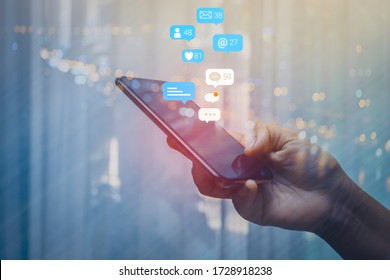 Person using a social media marketing concept on mobile phone with notification icons of like, message, comment and star above smartphone screen. - Shutterstock ID 1728918238