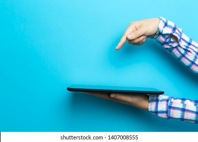 Person using a tablet computer device on a blue background