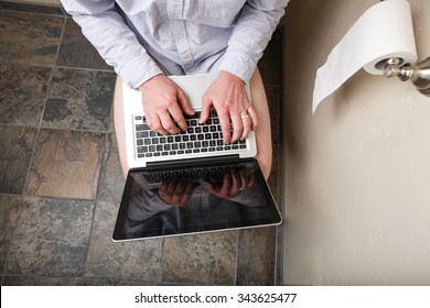 A person using their computer while on the loo
