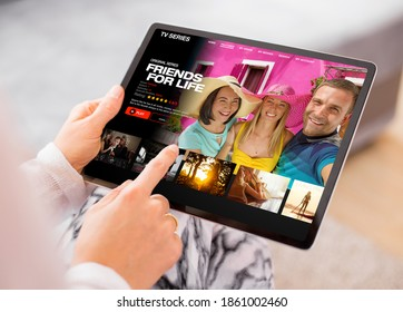Person using video streaming app on tablet and browsing movies and TV series to watch