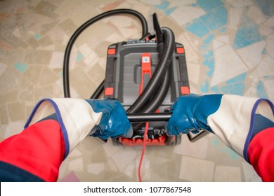 A person vacuums the construction site. Closeup of cleaner in special clothes and rubber gloves holds a handle from a professional industrial vacuum cleaner