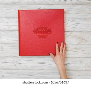 A person is viewing a photo album. Photo book with embossing. Photobook on a light surface. Red photo book with  leather cover.