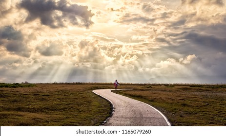 A person walking alone along s-shape path. The sun produces amazing light rays across the sky. The image is simple and breathtaking. This image is suitable for background use or add quote above. - Shutterstock ID 1165079260