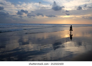 A person walking along a deserted beach at sunset, carrying an underwater camera and short flippers