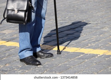 Person with walking cane standing on the street, shadow on pavement. Concept of limping man, old age, diseases of the spine, elderly people
