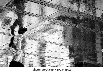 A person walking in the city pedestrian zone on a rainy day, from waist down, in black and white, with reflections