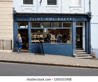 Person walking into  Flint owl Bakery on inclined High Street, Lewes, while through window can see barista taking coffee order from customer. Lewes, UK, September 12, 2019