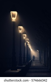 person walking on dark street illuminated with streetlamps