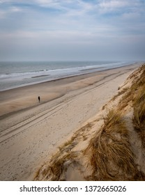 A person walking on an empty beach in the province Zeeland in the Netherlands