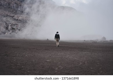 person walking towards the haze