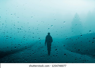 Person walks on rural foggy road during rainfall.