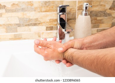 Person washing hands in white sink with inox water tap and soap container