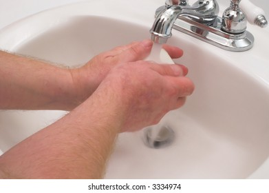 A person washing their hands with soap and water.