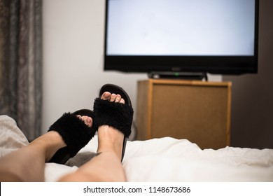 Person watches TV at night in his bed with his feet wearing black Flip Flops. The TV screen is blank white in her bedroom