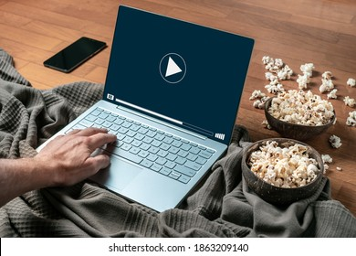 A person watching a movie or series in a laptop at home with popcorn. Concept of watching series or cinema by streaming