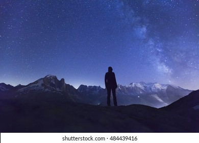 Person watching the stars and the Milky Way in the night sky above the Alps mountain range and the White Mount near Chamonix