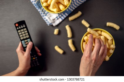 Person watching a TV and eat snacks, corn puffs. Relaxing, watching movies concept.