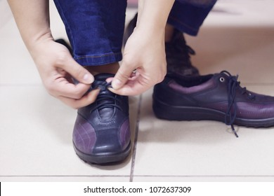 Person wear shoes tie shoelaces by oneself in the store boutique close up