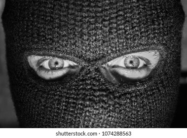 person wearing a balaclava with only the eyes showing.
