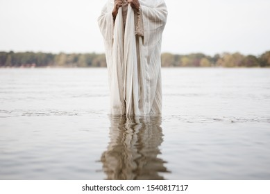 A person wearing a biblical robe standing in the water with a blurred background