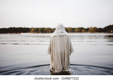 A person wearing a biblical robe walking in the water with a blurred background shot from behind