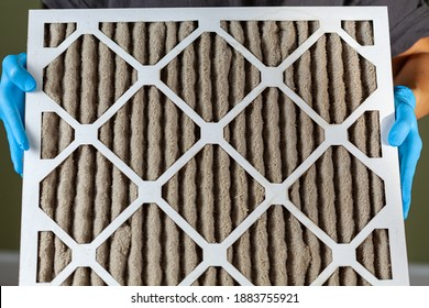 A person wearing blue gloves is holding a heavily clogged dirty air filter in hands before replacing it with the new one. Paper based, card board frame plated filters are used in hvac, ac , furnaces.
