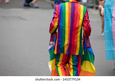 A person wearing a bright gay pride colourful jacket at a gay pride march
