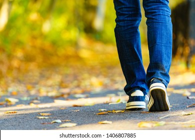 Person wearing casual sneakers shoes and blue jeans trousers walking outdoor. Stylish urban fashion details.