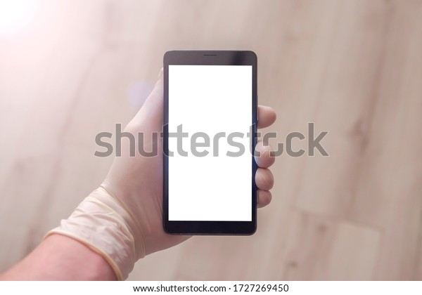 Person wearing disposable latex protective gloves while holding a mobile phone. One hand wearing a medical glove, holds a blank touchscreen smartphone. Mock up