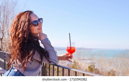 A person wearing glasses holding a glass of wine posing for the camera. Girl with curly hair, brunette with a glass of aperol cocktail by the sea. The concept of tourism and travel. Soft focus