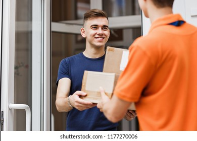 A person wearing an orange T-shirt is delivering parcels to a sa