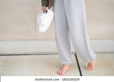 Person wearing sweatpants and holding white sneakers in one hand
