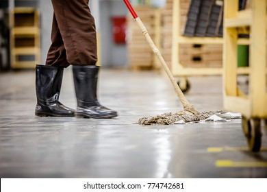A person wearing wellington boots pushes a mop in a factory/industrial work space.  The mop handle has been repaired with tape.