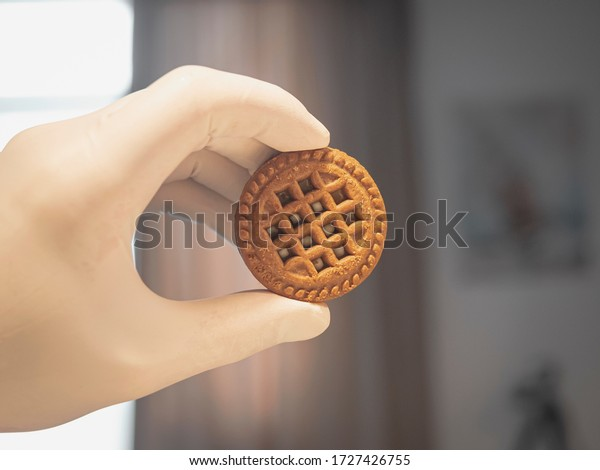 Person wearing white disposable latex gloves and holding round cookie. Hand with white surgical glove, holding freshly baked biscuit. Baked cookies filled with chocolate cream. Blurry background