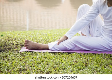 Person in white dress doing Yoga exercise on green grass near pond , morning light