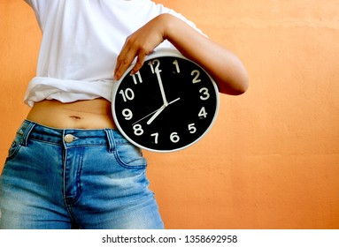Person in white shirt blue jeans pants and shows belly fat, holding clock in orange background