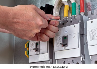 A person or worker screws an electric circuit breaker with a key to the circuit Board in the electrical Cabinet. Three powerful switches are fixed in a row. Switches are connected to cables or wires.