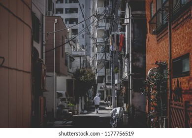 Person in working clothes walkin down an empty alley in Tokyo, Japan