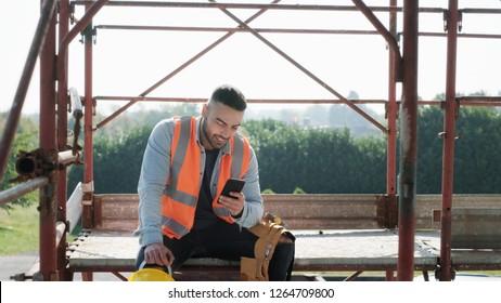 Person, die auf der Baustelle arbeitet. Weißer junger Mann bei der Arbeit im neuen Haus, lächelnd und Smartphone für Internet und soziale Medien während der Pause benutzen