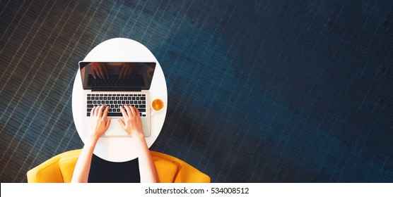 Person working on a laptop computer in a modern room - Shutterstock ID 534008512