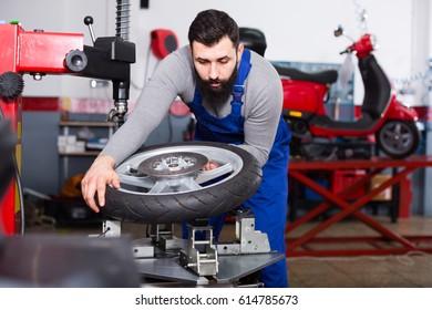 Person is working at restoring wheel in motorcycle workshop.