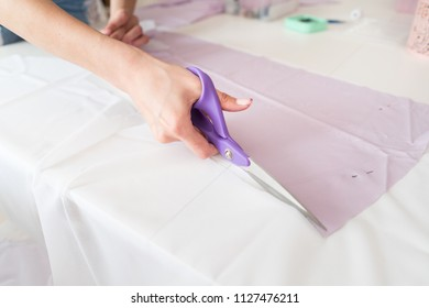 Person working. Seamstress woman sews the blouse.