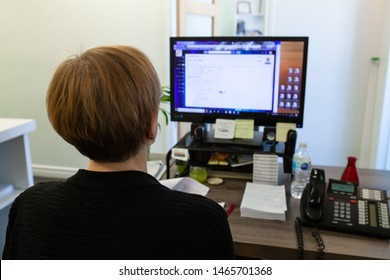 Person works on computer at office desk. A close up view of a lady worker sat a computer desk concentrating on PC screen. Back of head visible at a busy desk. Workplace employee carries out IT duties.