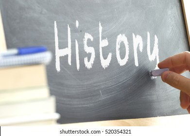 A person writing in a blackboard during History class in a school.