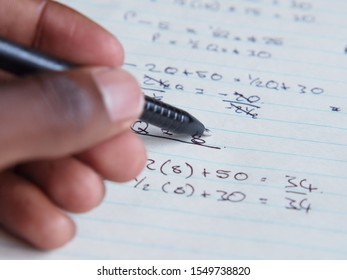A person writing a math problem with a black pen