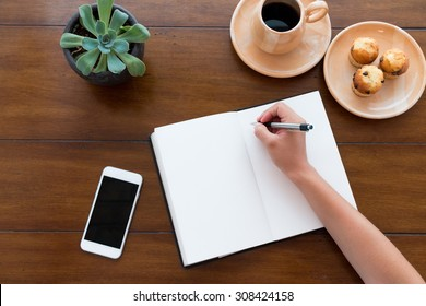 A person writing on her white notebook next to her smarth phone on a beautiful new wooden table with coffee and muffins