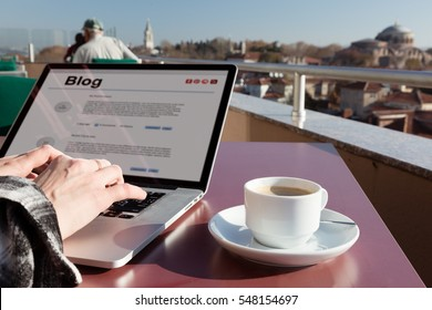 Person writing social Media article on Laptop Computer at table of Roof top Cafe in Istanbul City