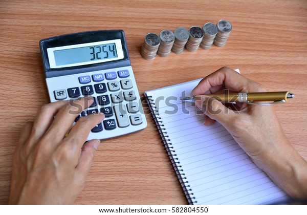 person writing and using calculator beside stack coins for finance and business