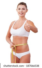 Personal achievement. Beautiful mature woman in underwear measuring her waist with measuring tape and showing her thumb up while standing isolated on white