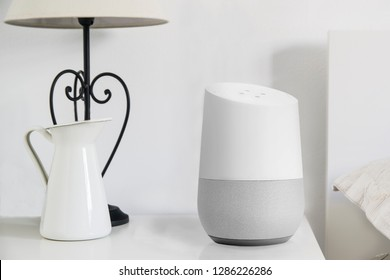 Personal assistant loudspeaker on a white wooden shelf of a smart home living room. Next, a book. Empty copy space for Editor's text.